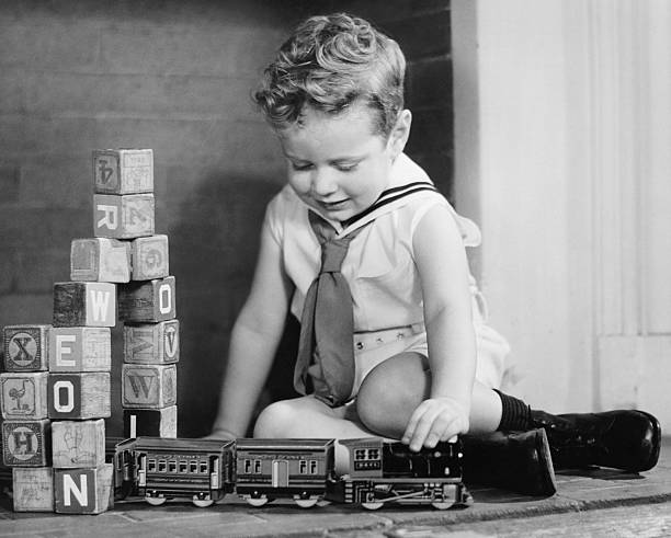 Boy (4-5) playing with model train set on floor, (B&W),  sailor suit stock pictures, royalty-free photos & images