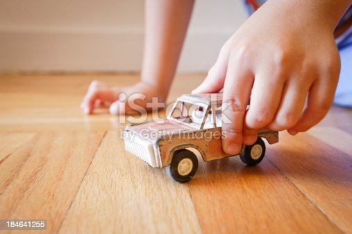 184659330 istock photo Boy playing with old red toy SUV truck 184641255