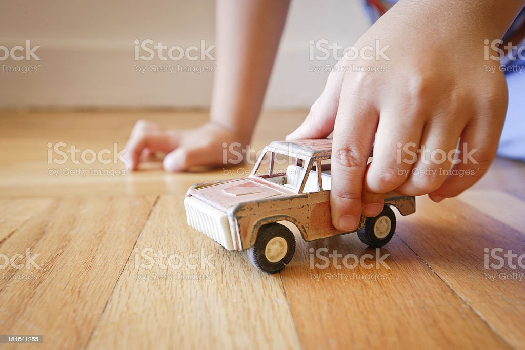 Boy playing with old red toy SUV truck stock photo