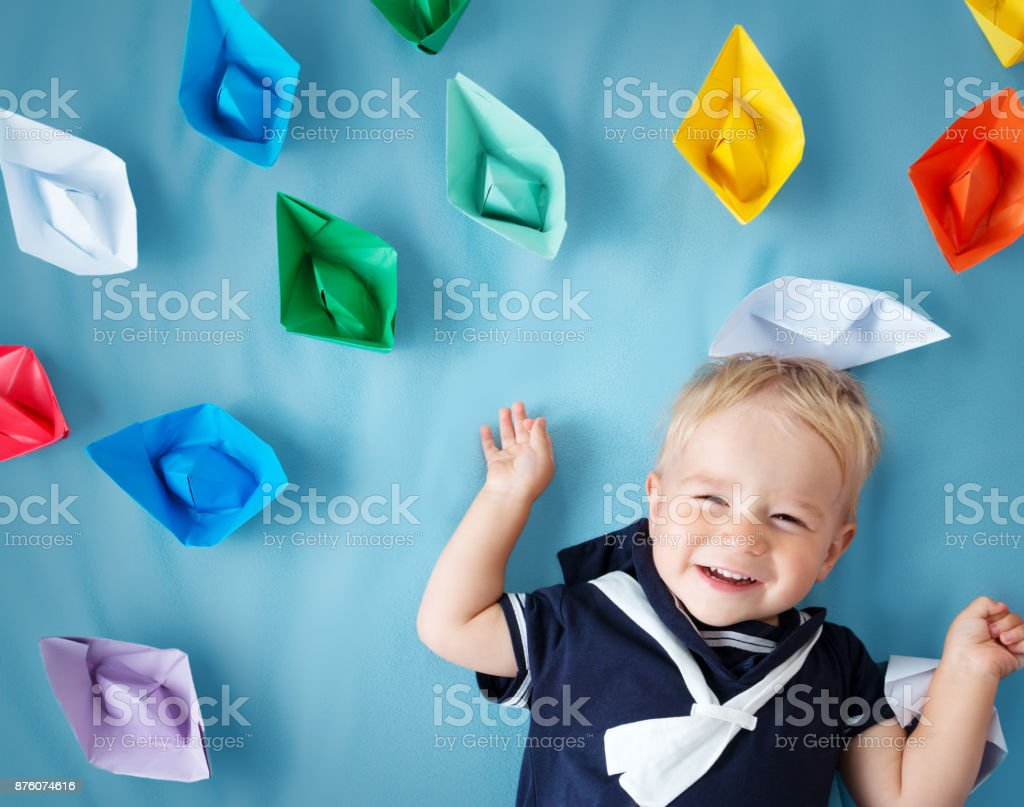 boy playing with paper ships stock photo