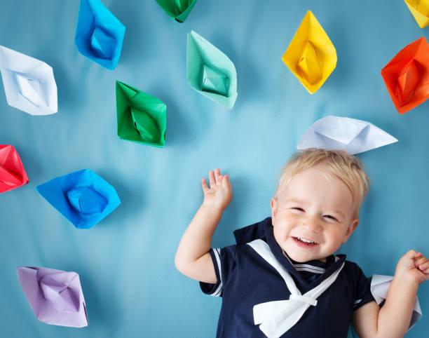 jungen spielen mit papier schiffe - matrosin kostüm stock-fotos und bilder