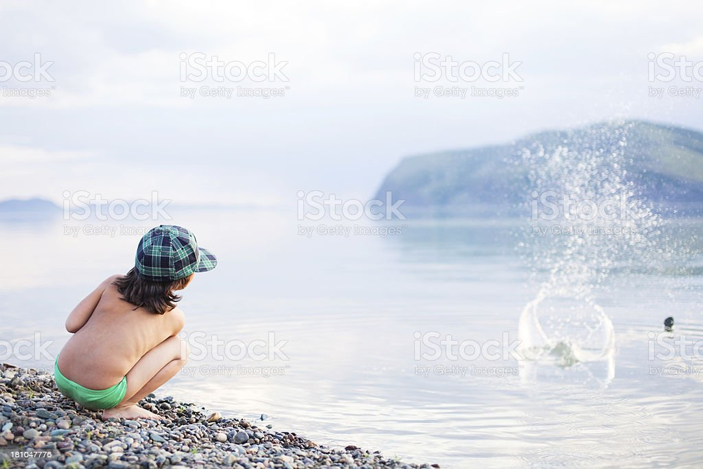 boy playing with pebbles on a beach stock photo