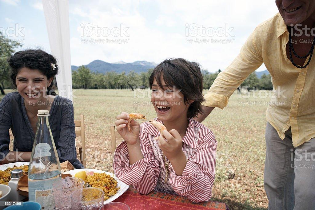 Petit garçon jouant avec des crevettes à la table à l'extérieur photo libre de droits