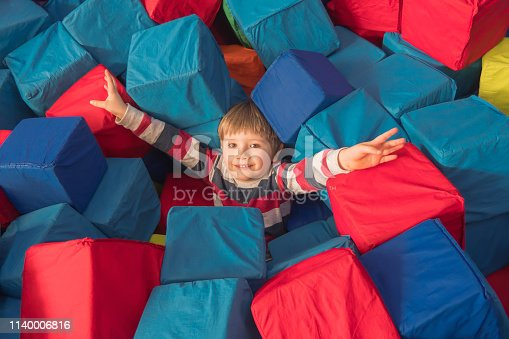 544818734 istock photo Boy playing with soft cubes in dry pool of the game children's room for birthday. entertainment centre. indoor playground in foam rubber pit in trampoline. Recreation for children 1140006816