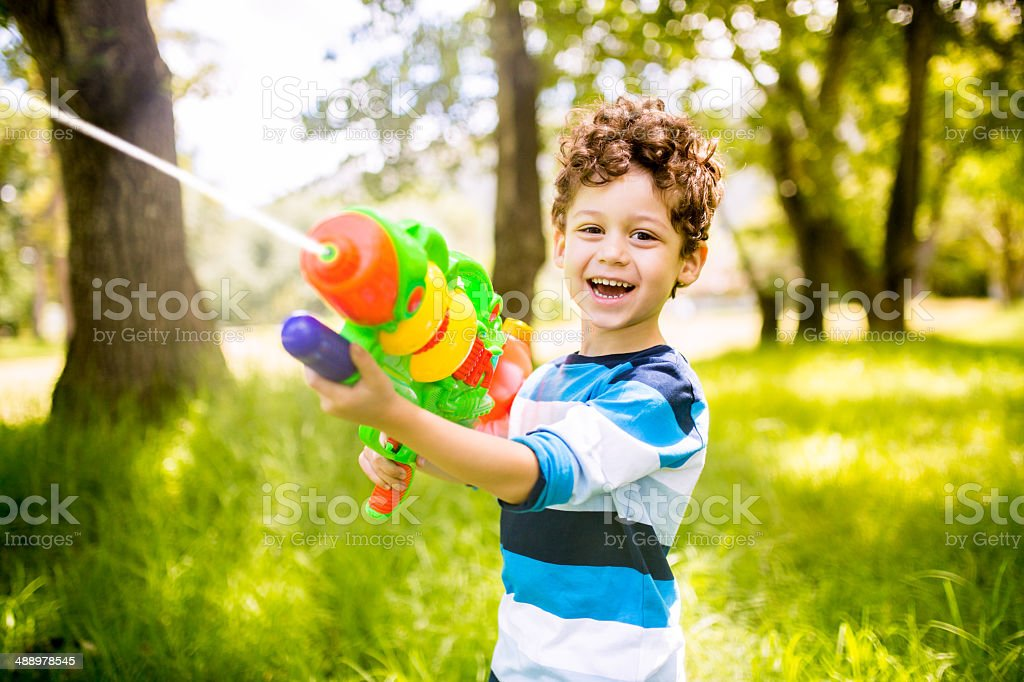 Boy playing with squirt gun stock photo