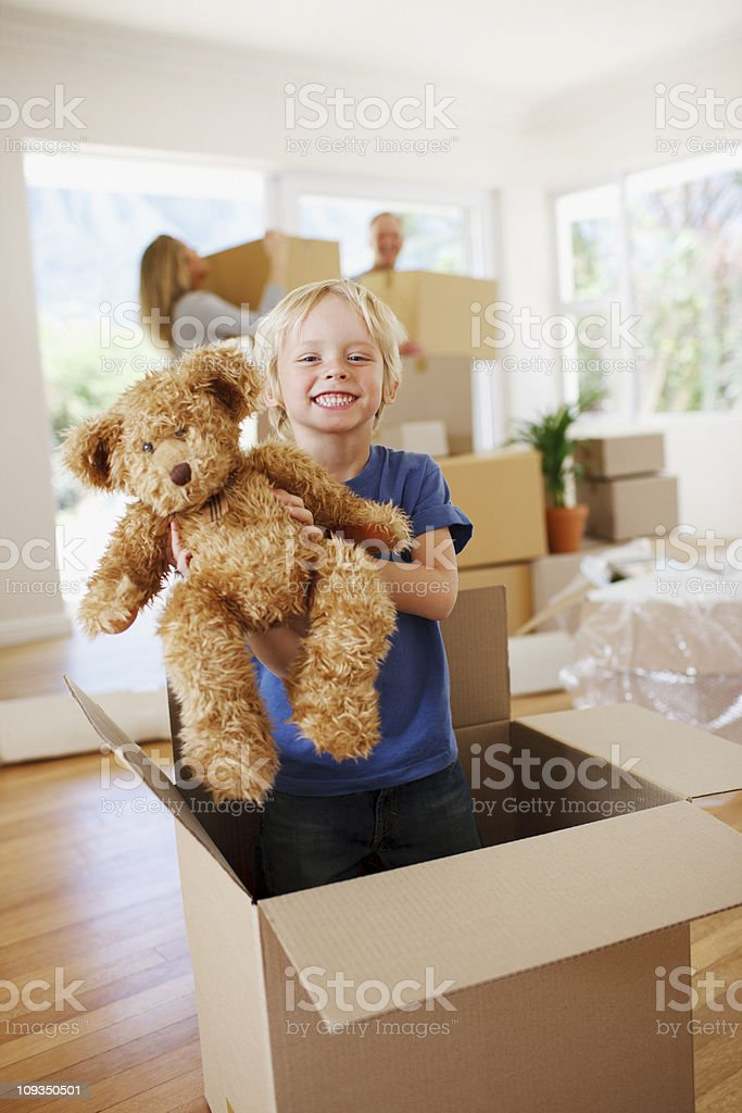 Boy playing with teddy bear in box in new house stock photo