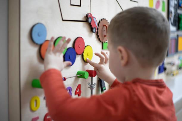 junge spielt mit dem interaktiven brett - autismus stock-fotos und bilder