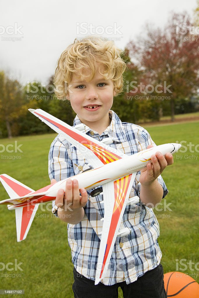 Boy playing with toy airplane outdoors royalty-free stock photo