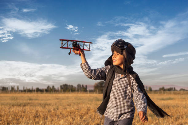 Boy playing with toy airplane Boy playing with toy airplane flight suit stock pictures, royalty-free photos & images