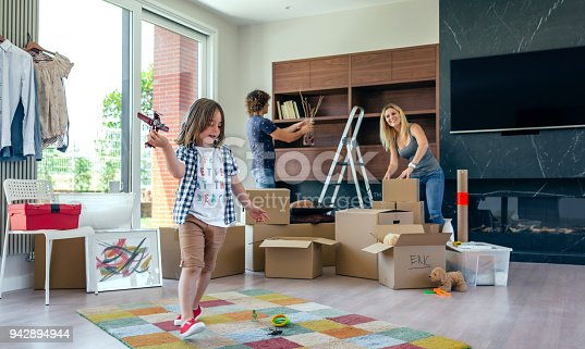 942256562istockphoto Boy playing with toy airplane while parents unpack 942894944