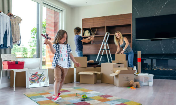 boy playing with toy airplane while parents unpack - happy mom packing some toys stock photos and pictures
