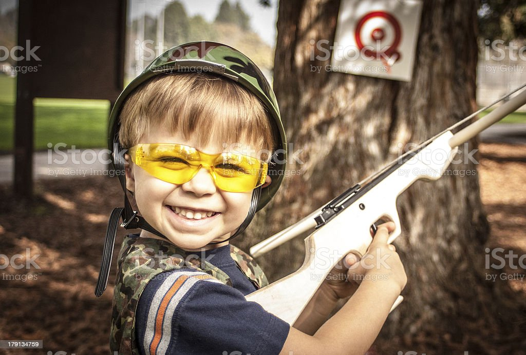 Boy Playing with Toy Crossbow Gun stock photo