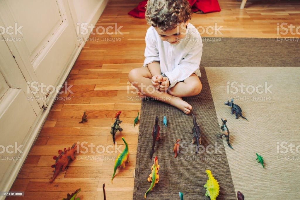 Menino brincando com brinquedos de dinossauros - foto de acervo