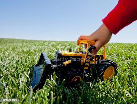 A boy with a red sweatshirt is playing with a toy front loader bulldozer on the grass during the day.
