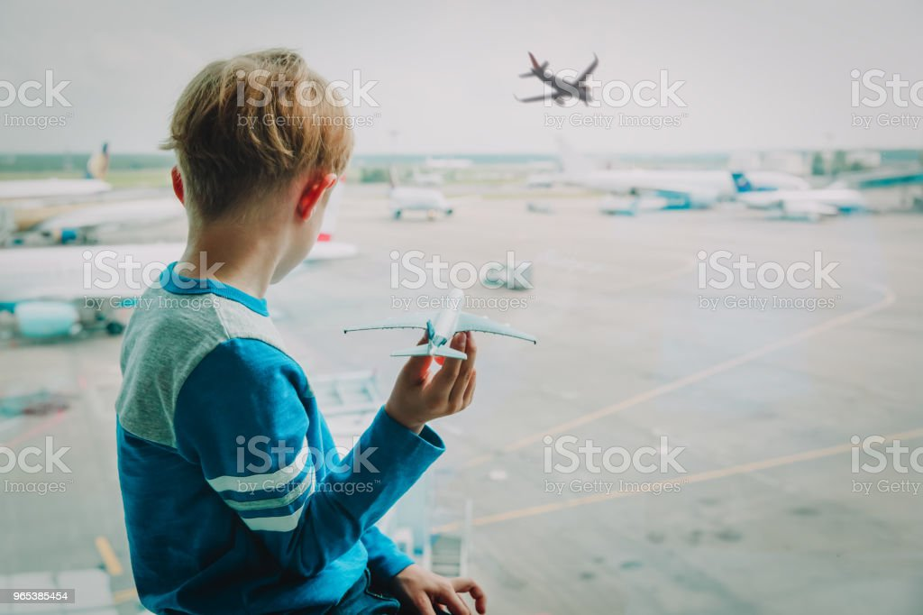 boy playing with toy plane while waiting in airport royalty-free stock photo