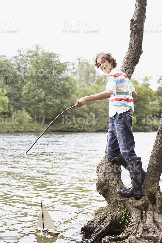 Boy playing with toy sailboat in lake royalty-free stock photo