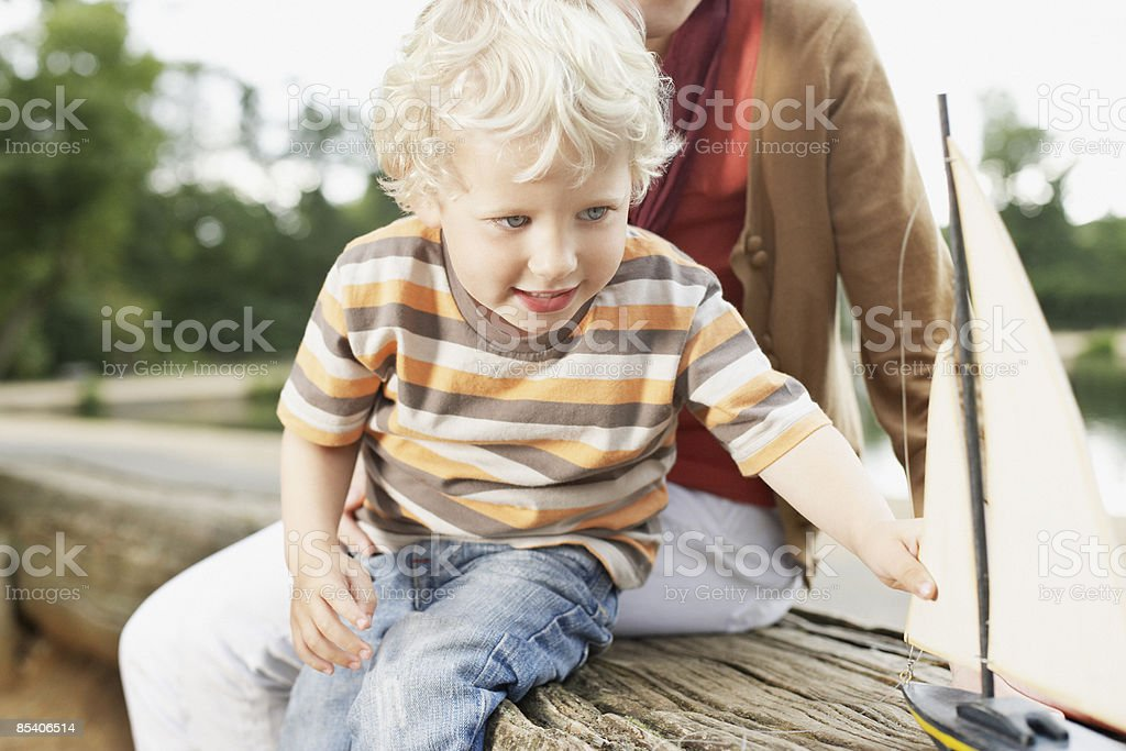 Boy playing with toy sailboat royalty-free stock photo