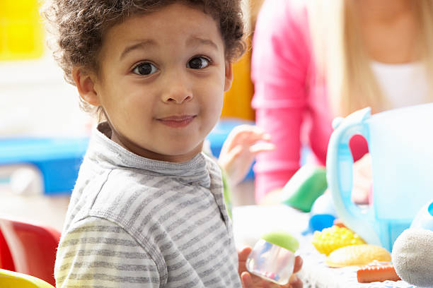 Boy playing with toys in nursery stock photo