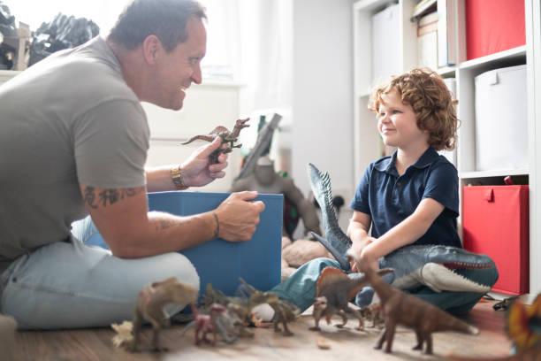 jungen spielen mit spielzeug mit seinem vater - kreativer speicher stock-fotos und bilder