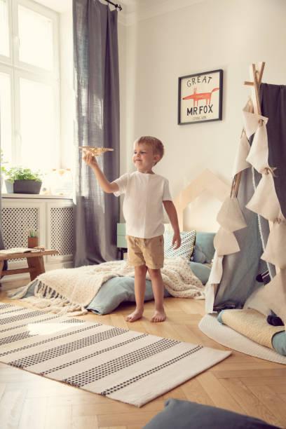 jungen spielen mit hölzernen flugzeug im skandinavischen schlafzimmer innenraum mit zelt und poster. echtes foto - fuchs kissen stock-fotos und bilder