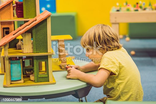 istock Boy playing with wooden house in kindergarten 1200447989