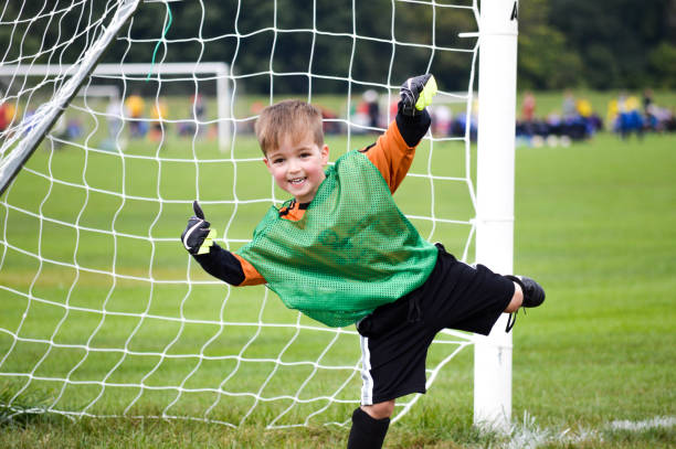 Boy playing youth soccer outdoors stock photo