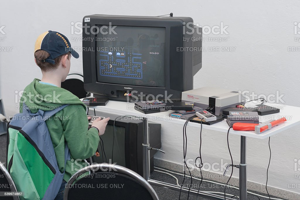 Boy plays gaming console with television at Animefest stock photo