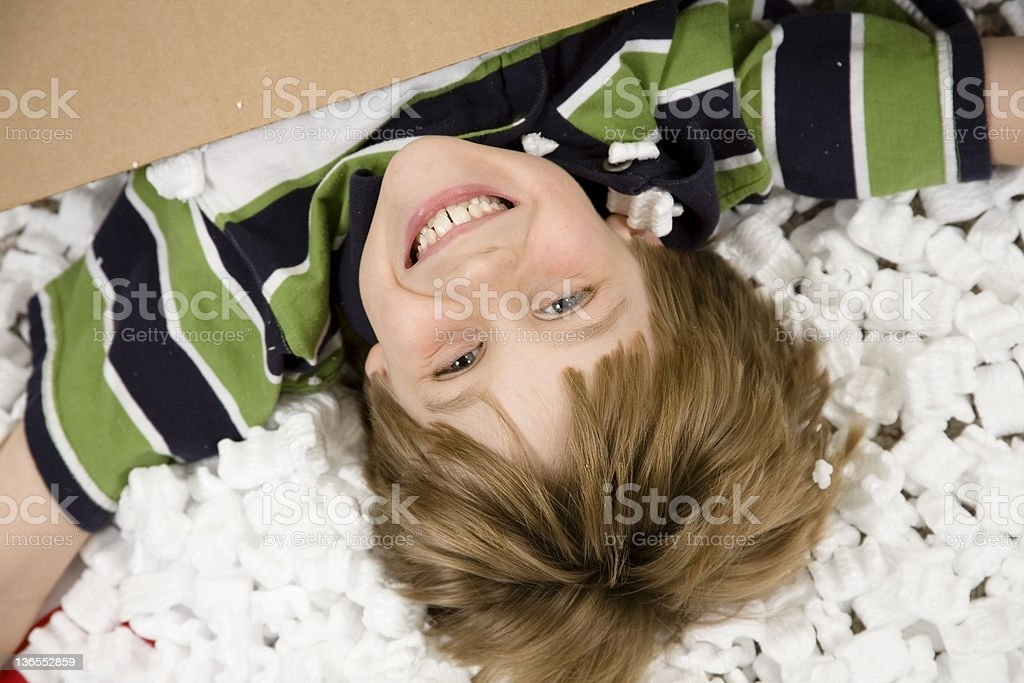Boy plays in packing peanuts, cardboard box. Unpacking, packing. Moving. royalty-free stock photo