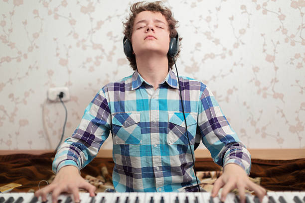 Boy plays piano A shot of teenager boy playing piano keyboard player stock pictures, royalty-free photos & images