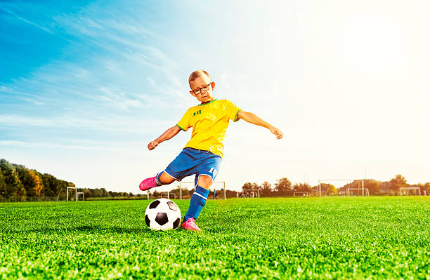 Boy plays soccer on field and kicks football stock photo