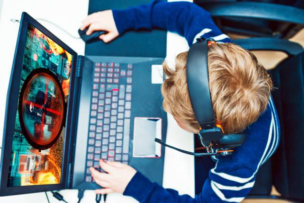 junge spielt videospiele auf gaming-computer während des tragens kopfhörer - online spiele spielen stock-fotos und bilder