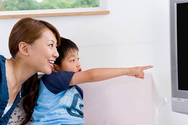 Boy pointing at TV monitor stock photo
