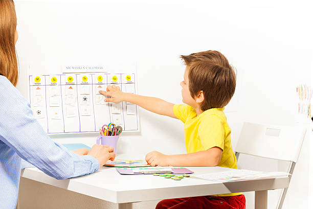 boy points at activities on calendar learning days - planeringskalender bildbanksfoton och bilder
