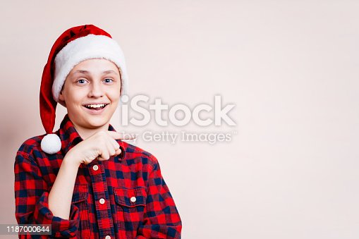 1045527172 istock photo boy points with index finger at empty space 1187000644