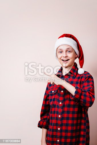 1045527172 istock photo boy points with index finger at empty space 1187000694