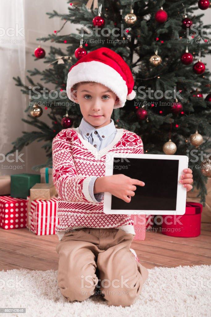 boy ponting at tablet on christmas stock photo