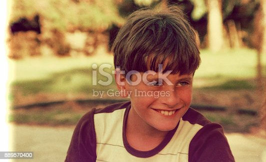 Vintage image of a boy smiling outdoors and looking away from camera
