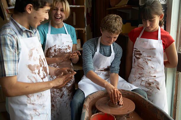 Boy (13-15) potting on wheel surrounded by classmates stock photo