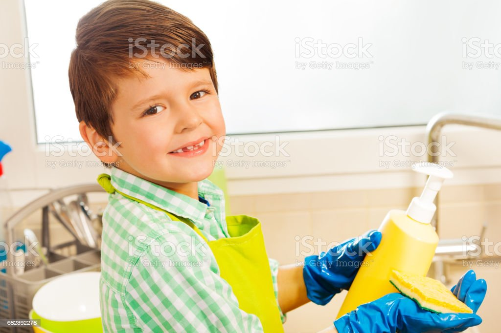Boy pouring dish soap on sponge in the kitchen royalty-free stock photo