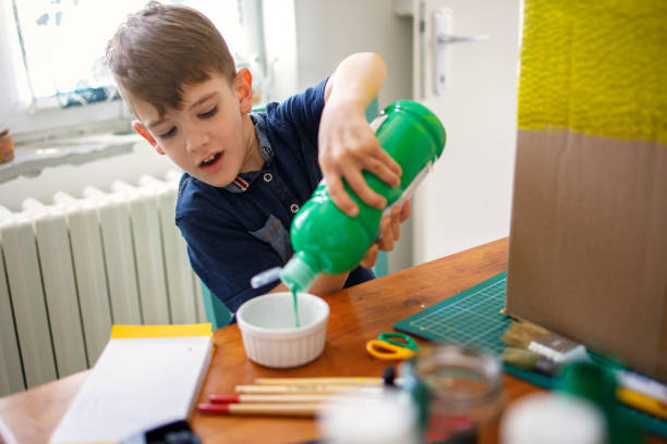Boy pouring green color, getting ready for paint stock photo
