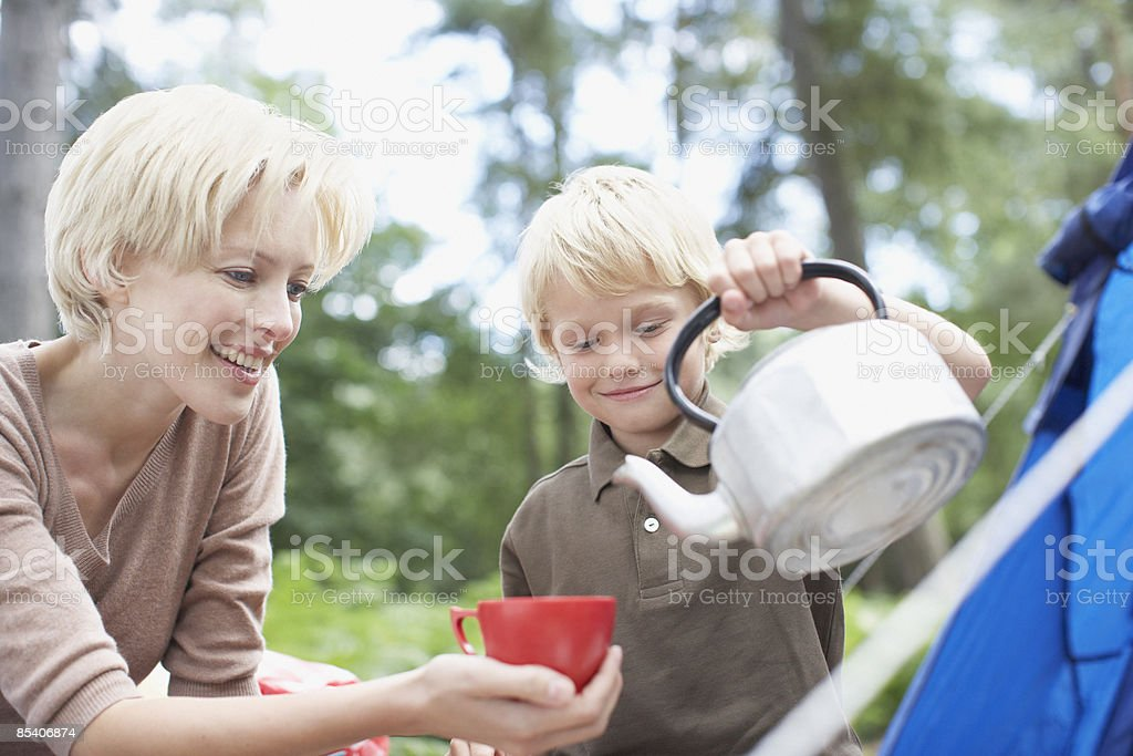 Boy pouring hot water for mother at campsite royalty-free stock photo