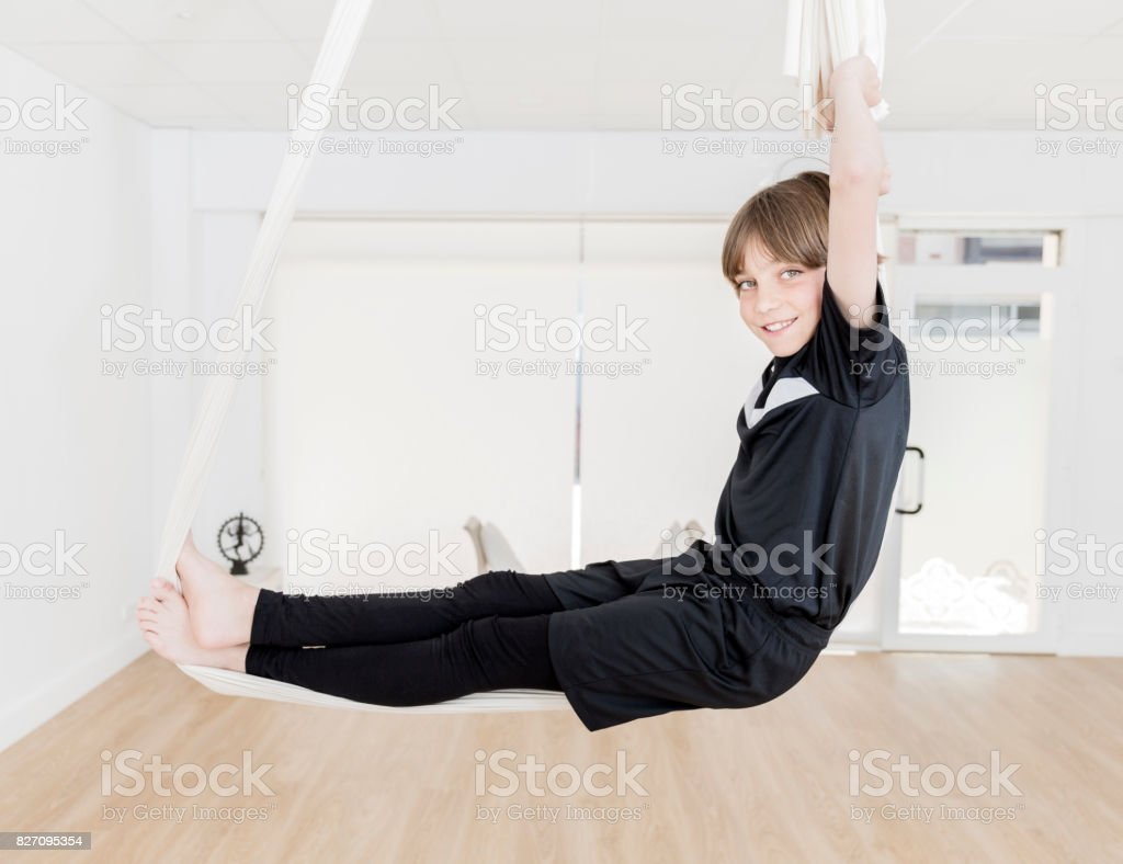 Boy practicing aerial yoga stock photo