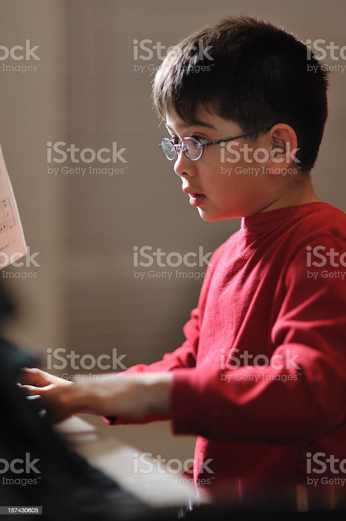 Boy practicing piano royalty-free stock photo