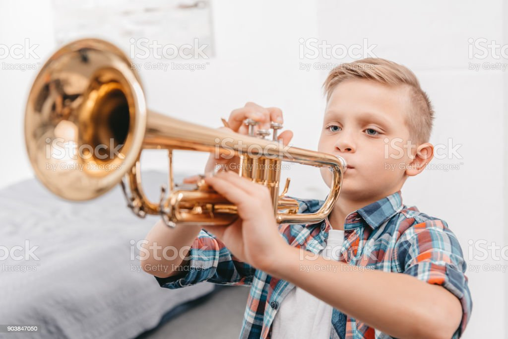boy practicing trumpet stock photo