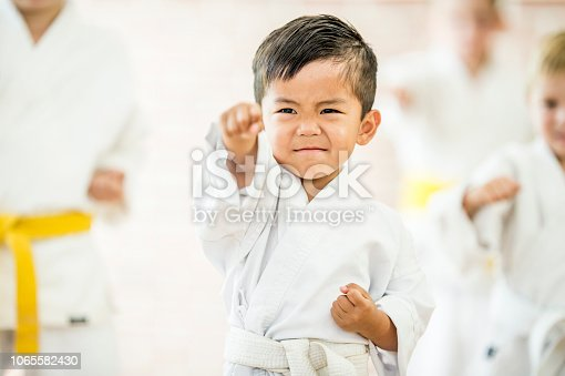A young asian boy in a karate uniform demonstrates his moves inside a martial arts studio.