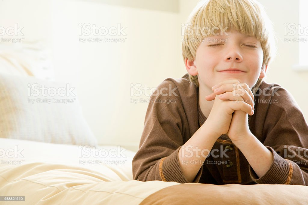 Boy praying alone at home in bedroom stock photo