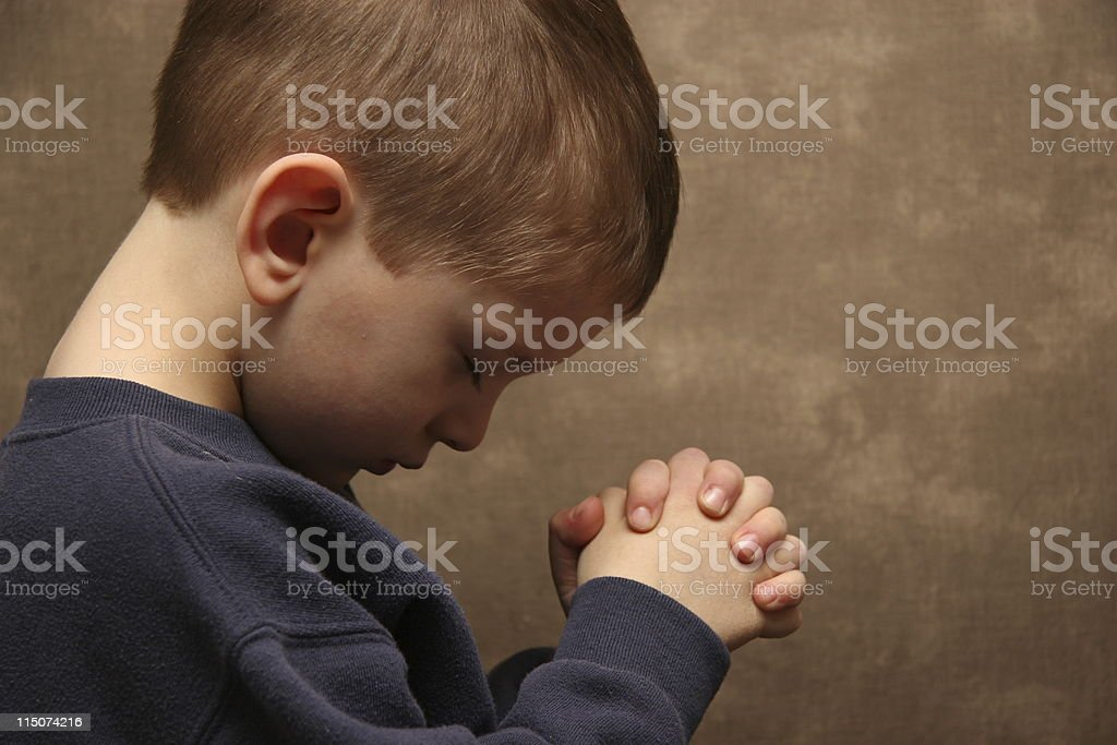 Boy praying - color stock photo