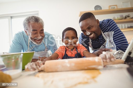 istock Boy preparing cookie dough with his father and grandfather in kitchen 837502608