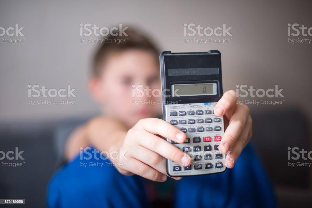 Boy presenting calculator stock photo
