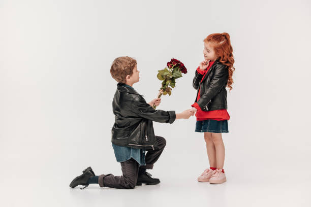 boy presenting roses bouquet to his little girlfriend while standing on knee isolated on grey boy presenting roses bouquet to his little girlfriend while standing on knee isolated on grey cute teen couple stock pictures, royalty-free photos & images